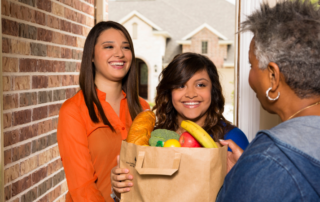 Two women bringing food to an older adult